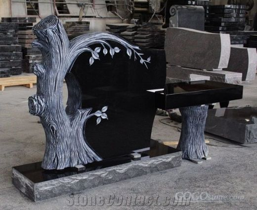 black granite headstone with trees